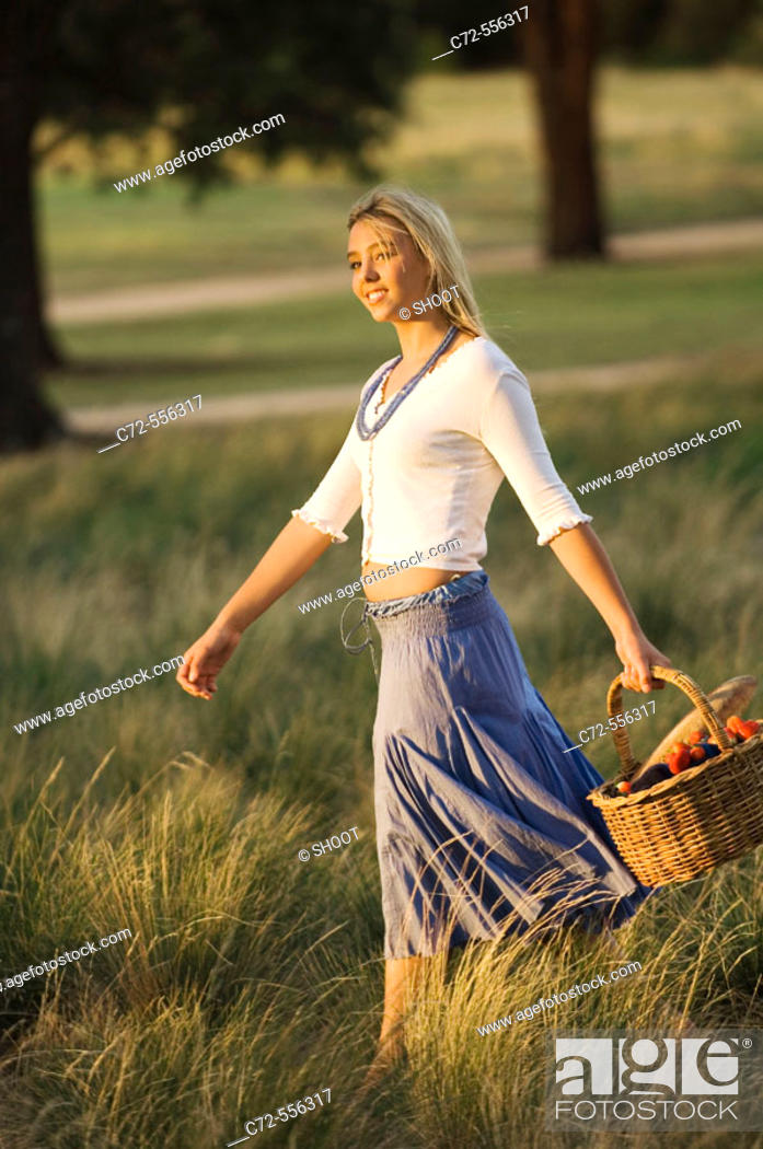 Stock Photo: Teenage girl walking in feild, holding basket.