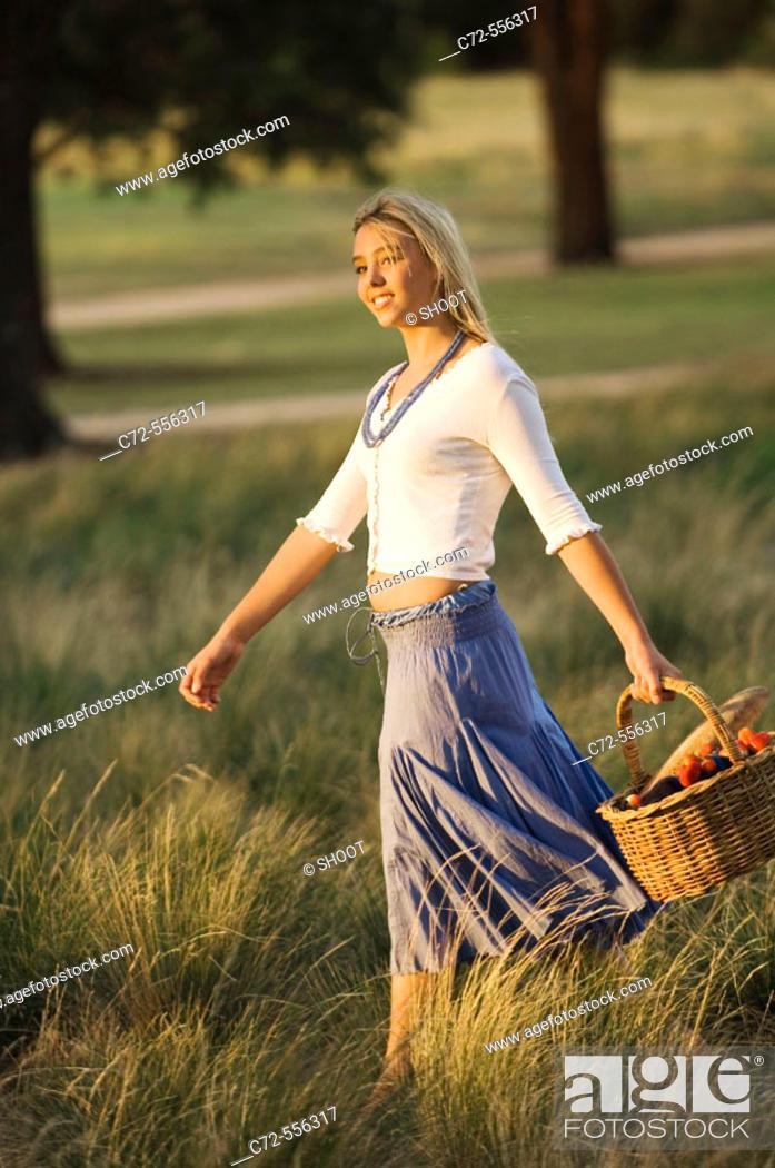 Stock Photo: Teenage girl walking in feild, holding basket.