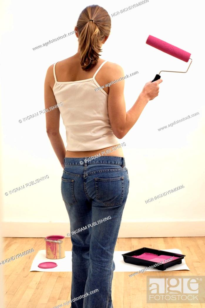 Stock Photo: Rear view of a young woman holding a roller brush.