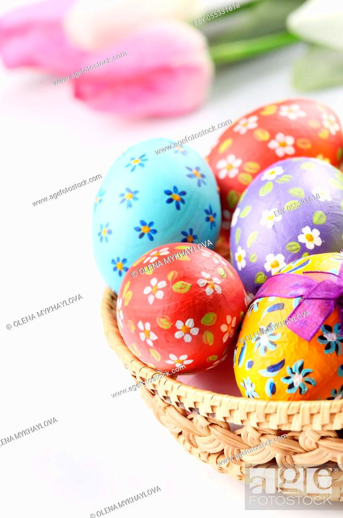 Stock Photo: Easter decorations - flowers, basket with painted eggs on white.