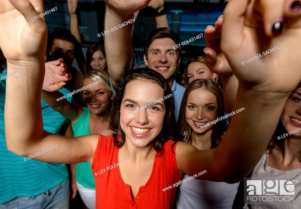 Stock Photo: party, holidays, celebration, friends and people concept - smiling friends dancing and waving hands in club.