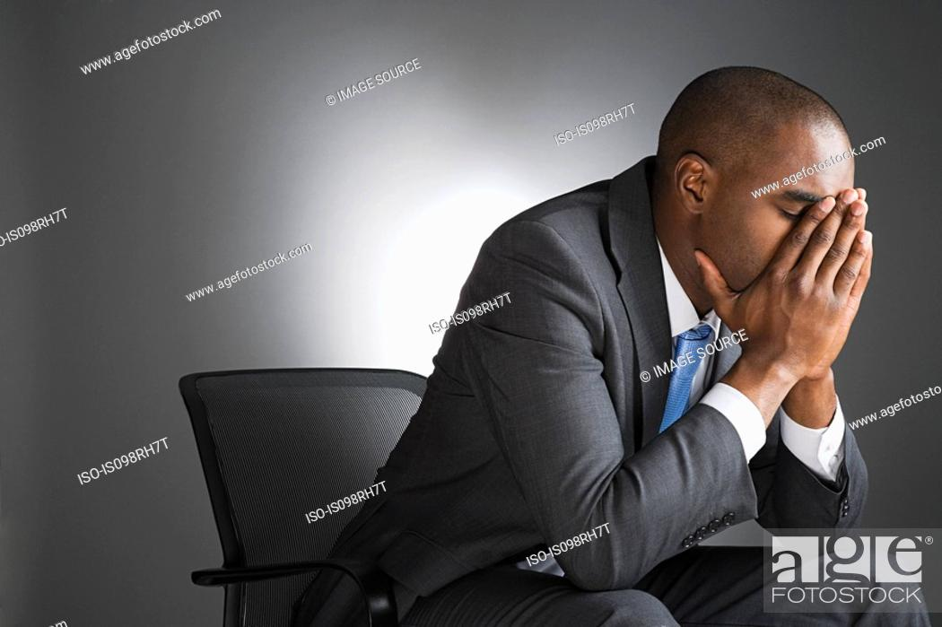 Stock Photo: Businessman with head in hands.