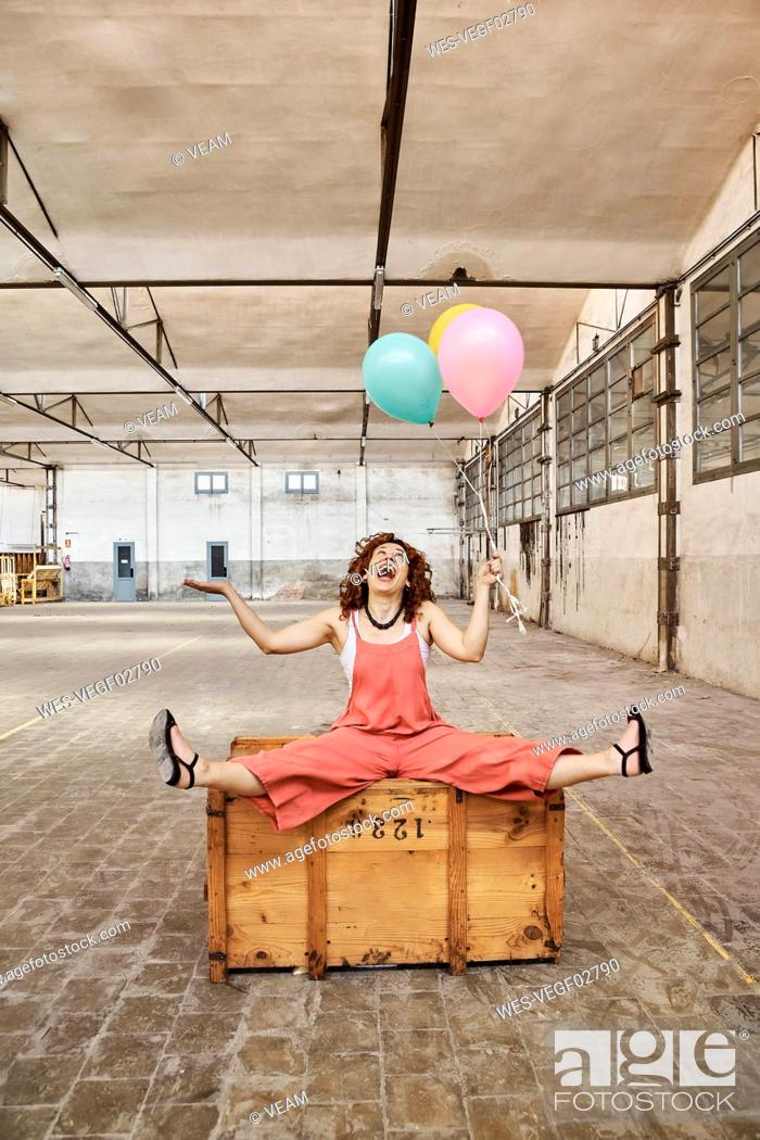 Stock Photo: Cheerful woman playing with colorful helium balloons while sitting on wooden box.