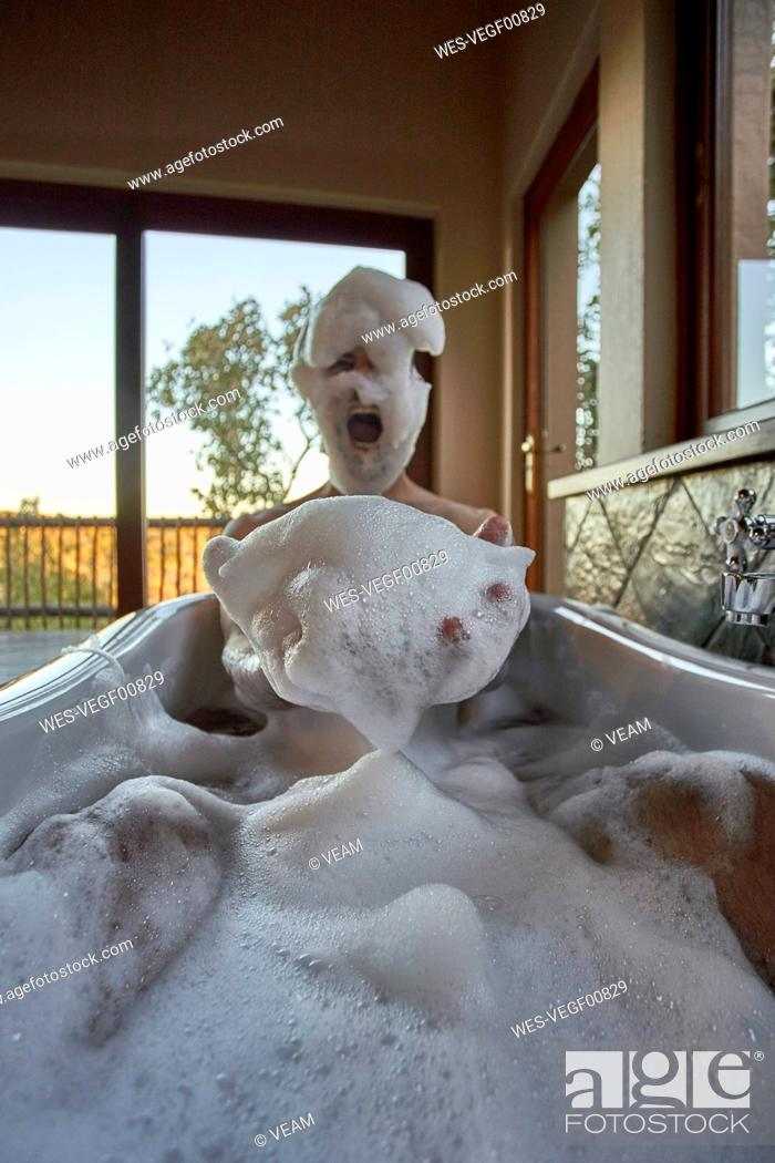 Stock Photo: Man playing with the foam in a bathtub.