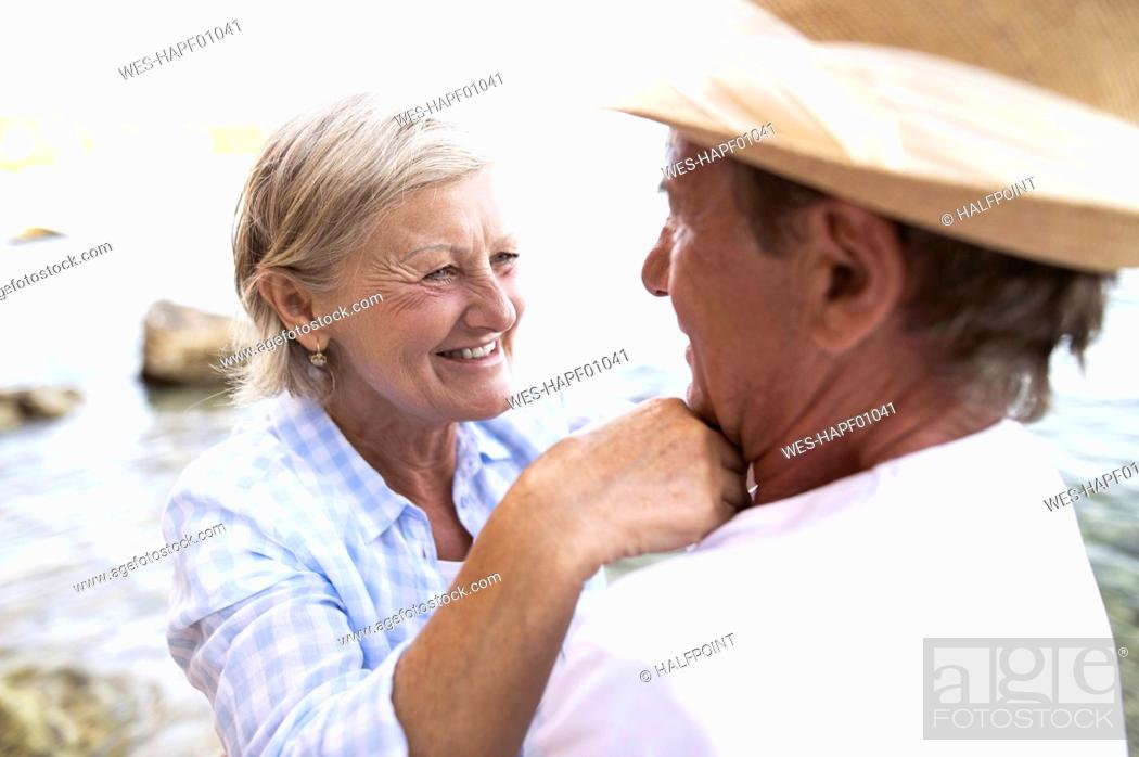 Stock Photo: Happy woman face to face to her husband in front of the sea.