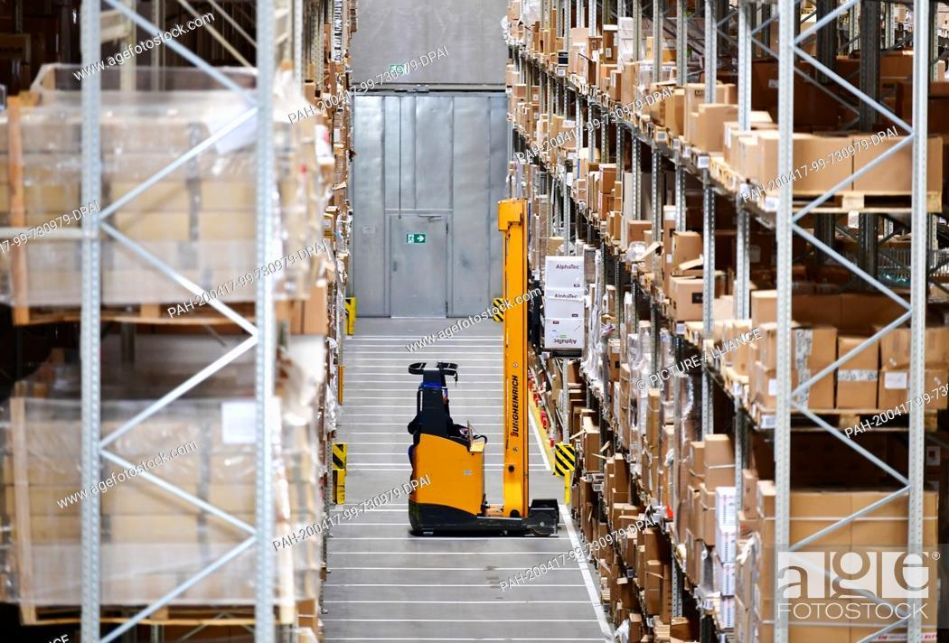 Stock Photo: 16 April 2020, Brandenburg, Großbeeren: A Jungheinrich electric high-bay truck is driving at the logistics service provider Rhenus Warehousing Solutions SE & Co.