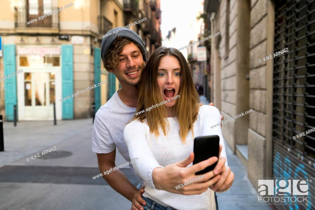 Stock Photo: Happy young couple taking a selfie the city.
