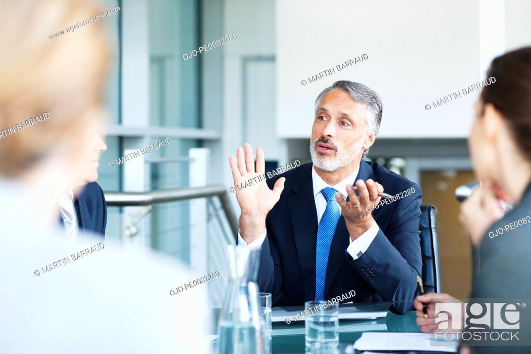 Stock Photo: Gesturing businessman leading meeting in conference room.