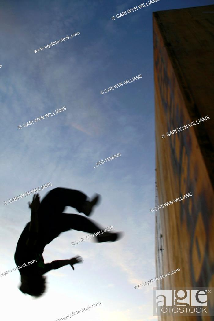 Stock Photo: man performing parkour on roof top in city town at night.
