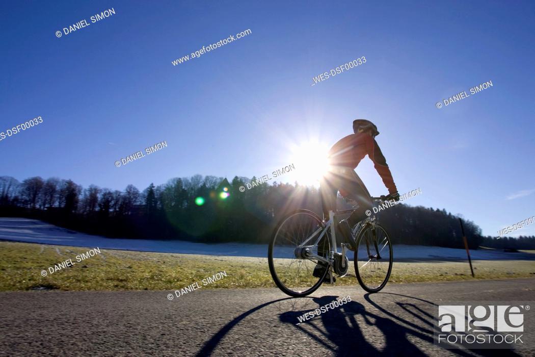 Stock Photo: Germany, Bavaria, Oberland, Man mountain biking, rear view.