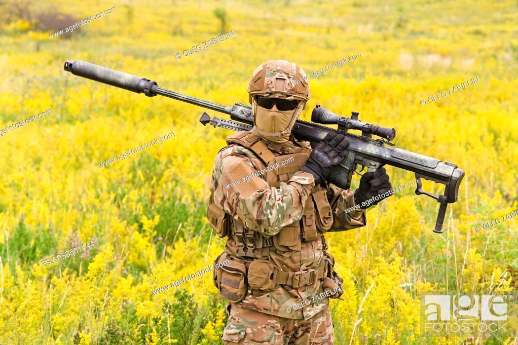Imagen: Soldier with big sniper rifle walks across blooming field.