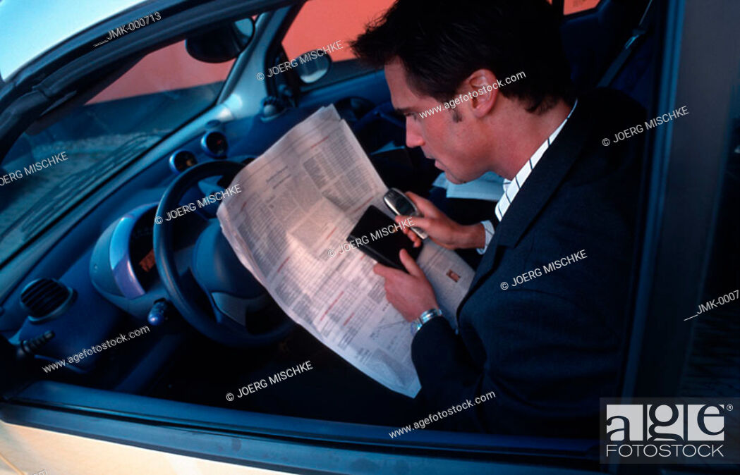 Stock Photo: A salesman, businessman, tradesman, employee, officer, young man sitting in a car reading a newspaper.