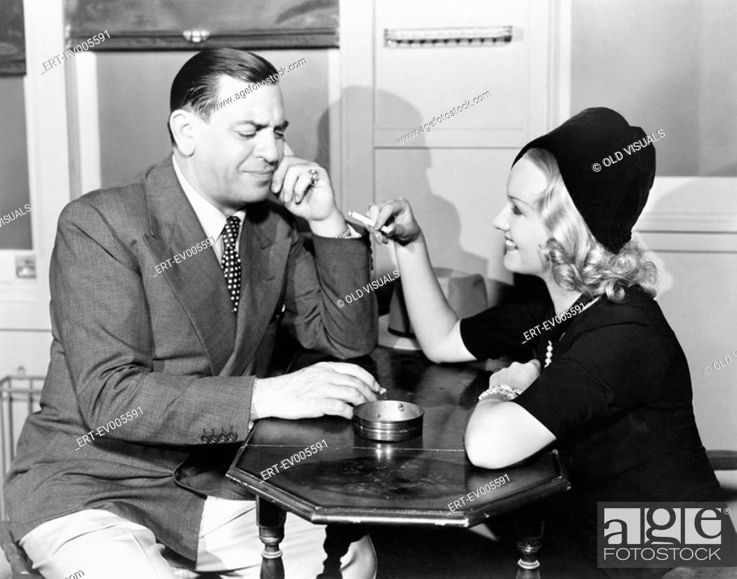 Stock Photo: Profile of a man with a young woman smoking sitting in a cafe All persons depicted are not longer living and no estate exists Supplier warranties that there.