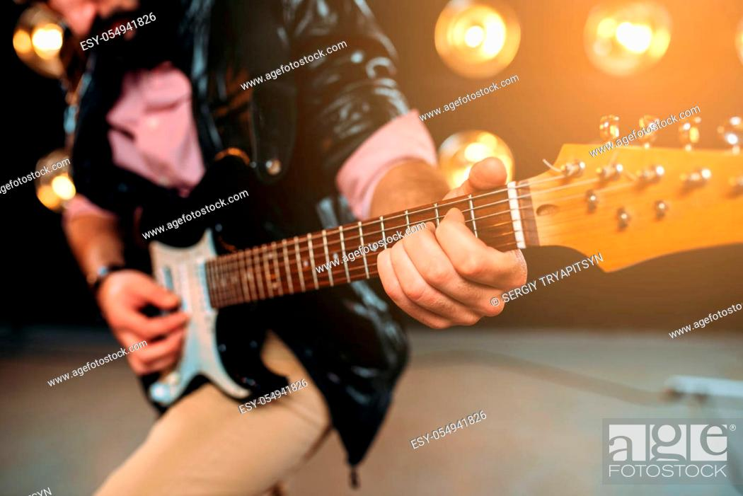 Imagen: Male guitarist hands performing music on the stage with the decorations of lights. Musical solo concert.