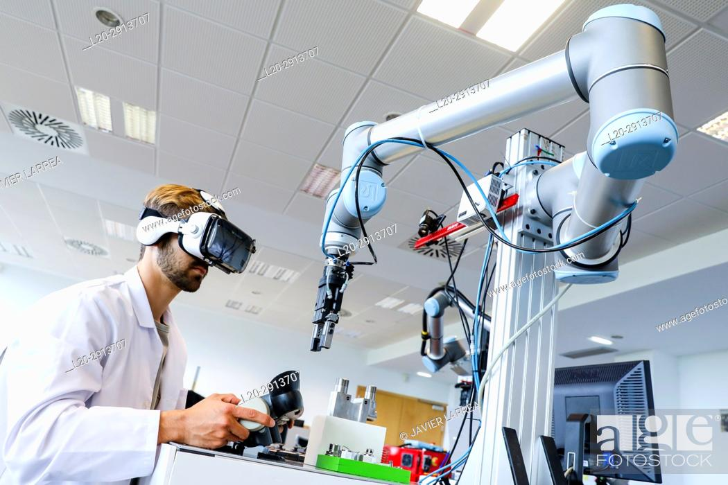 Stock Photo: Researcher with virtual reality glasses, VR, Humanoid robot for automotive assembly tasks in collaboration with people, Industry, Tecnalia Research & innovation.