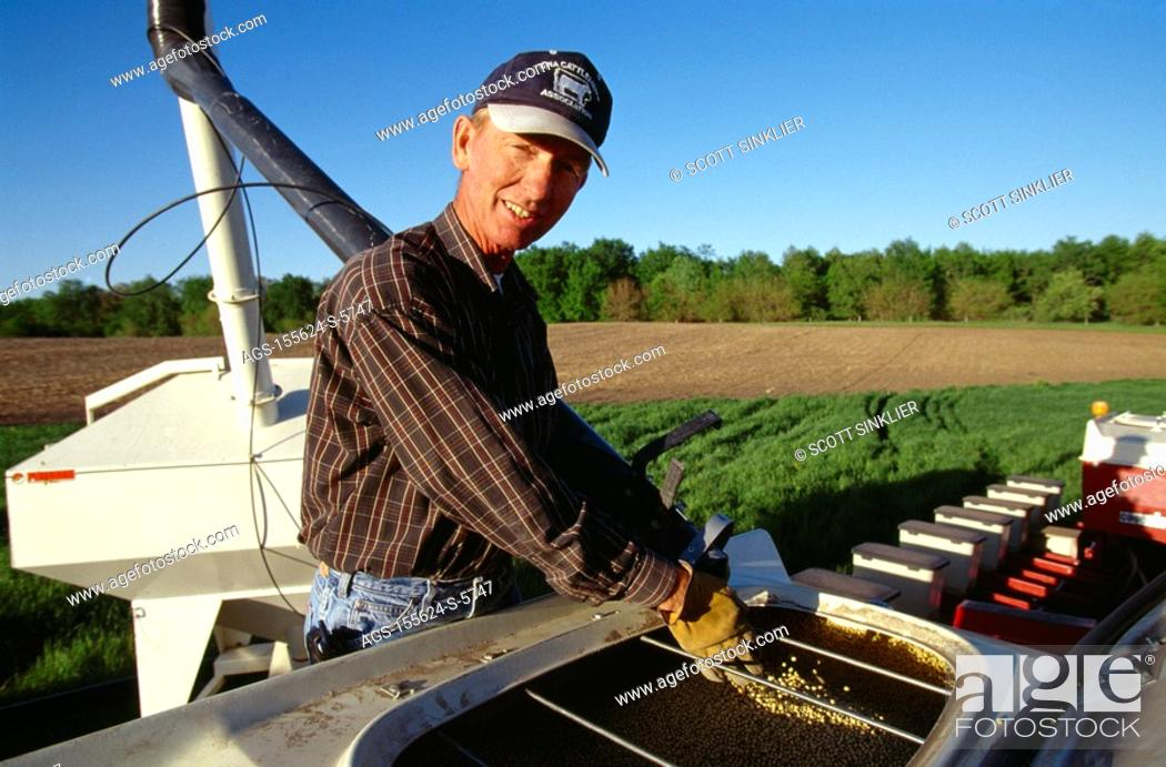 Agriculture - A farmer loads soybean seed into the seed