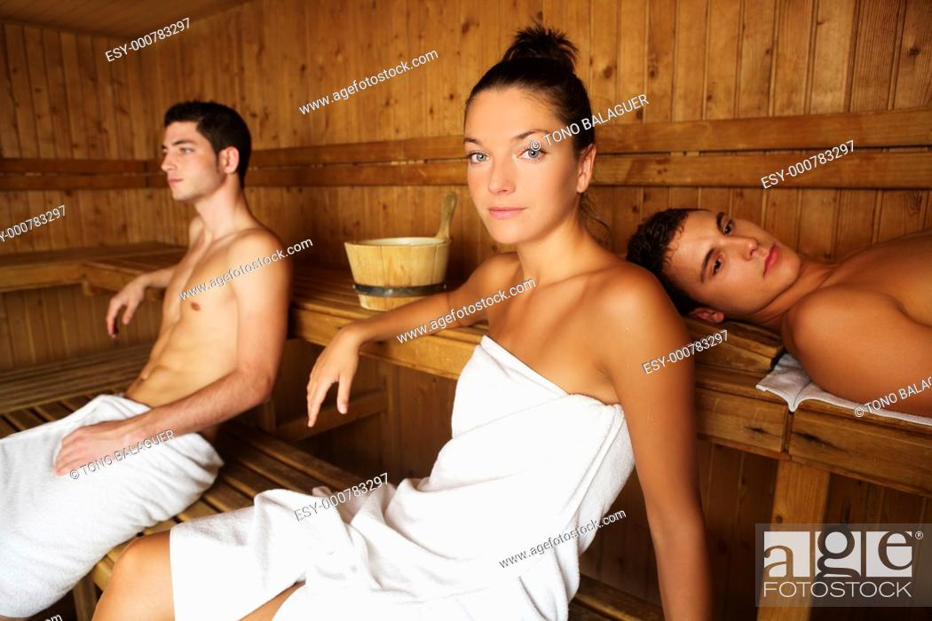 Photo de stock: Sauna spa therapy young people group in warm wooden room white towel.