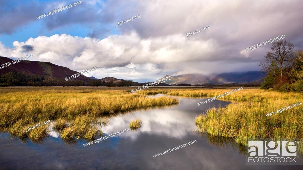 Stock Photo: A blaze of sunshine on the shores of Derwent Water and the distant hills of Latrigg, on a showery autumn afternoon, Lake District National Park, Cumbria.