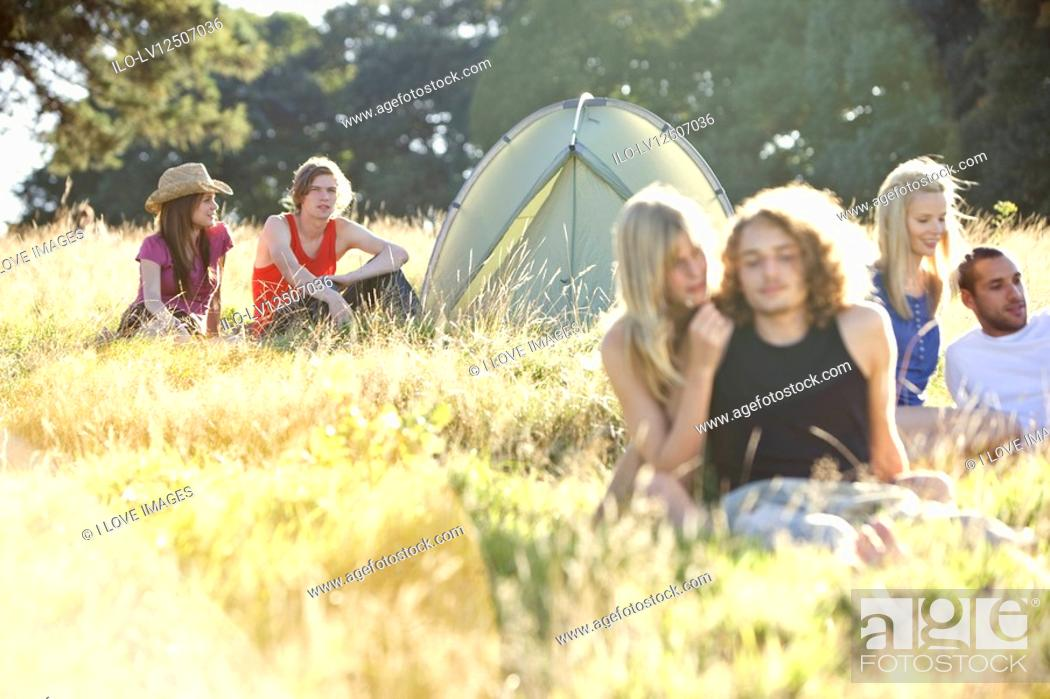 Stock Photo: Three young couples sitting in a field near a tent.
