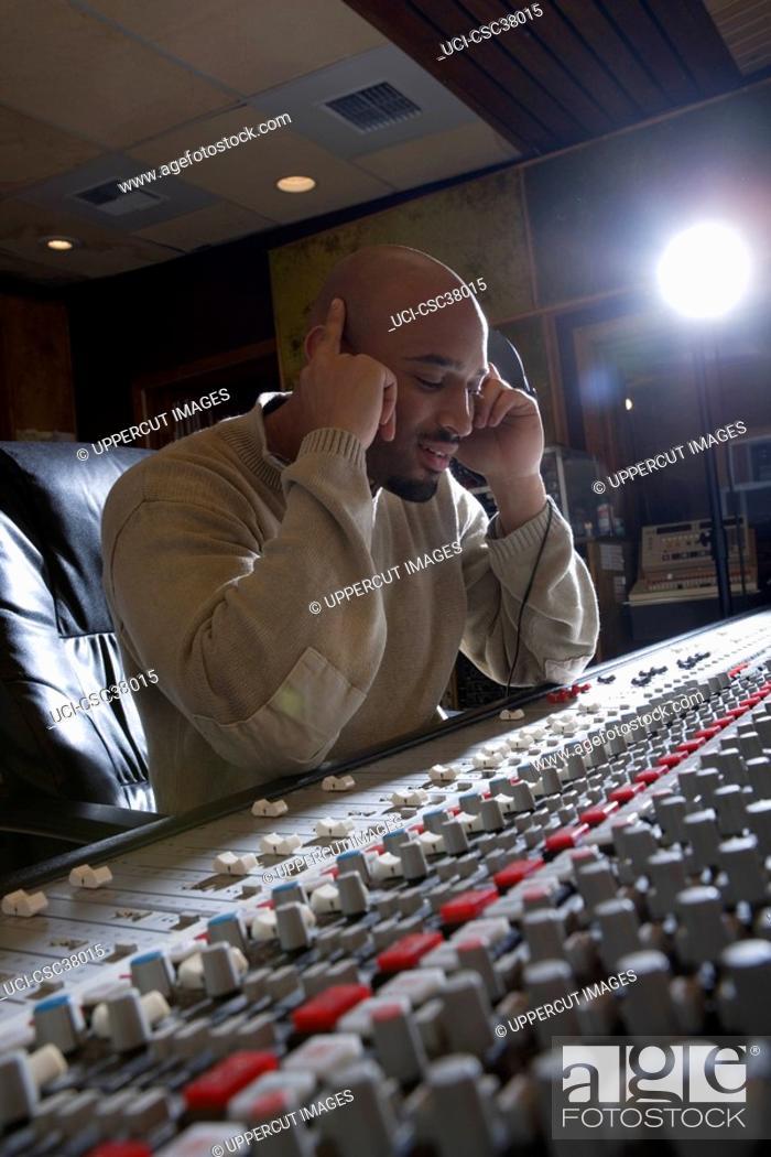 Stock Photo: Music producer listening to headphones.