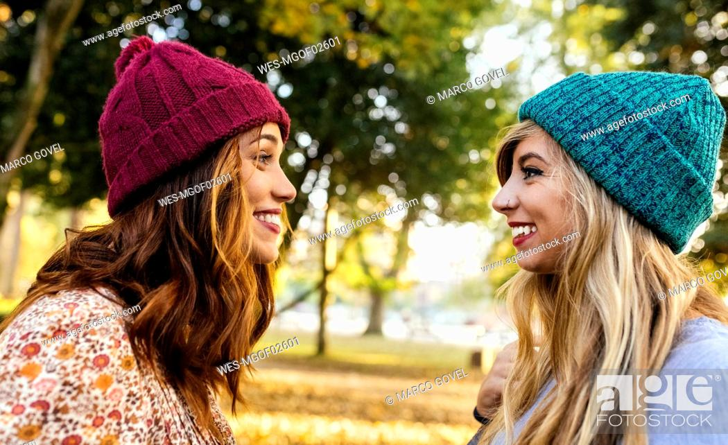 Stock Photo: Two smiling young women wearing wooly hats in a park in autumn.