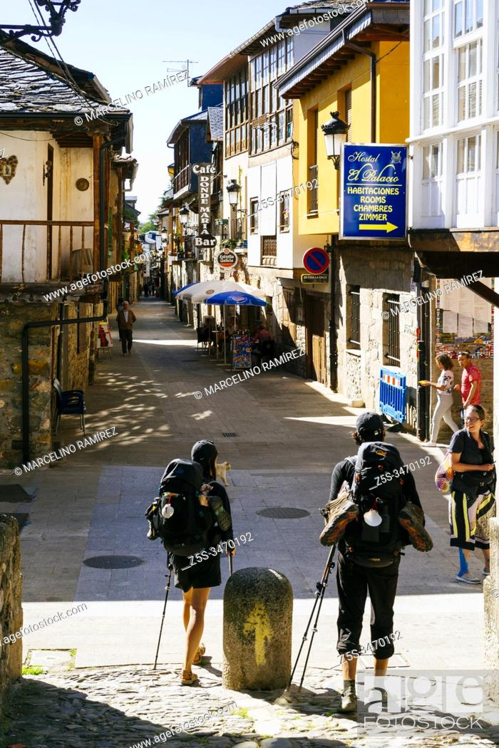 Stock Photo: Couple of pilgrims accessing the historic center of Molinaseca through Calle Real. French Way, Way of St. James. Molinaseca, El Bierzo, Leon, Castile and Leon.
