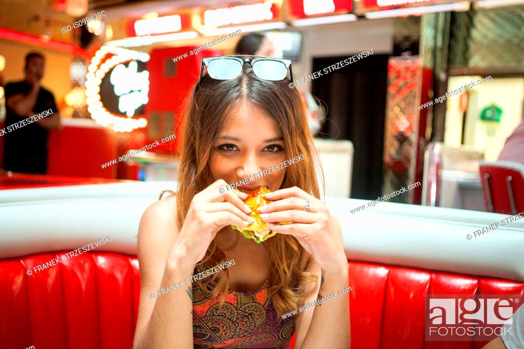 Stock Photo: Portrait of young woman sitting in diner, eating sandwich.