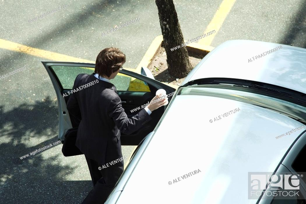 Stock Photo: Businessman getting into car.