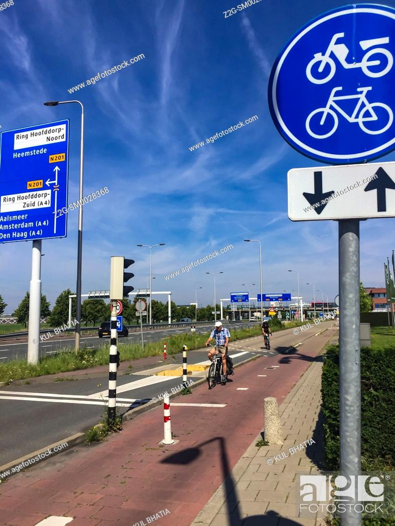 Stock Photo: A proper bike path, complete with grade separation and dedicated signals, next to a busy motorway, in Amsterdam, the Netherlands.