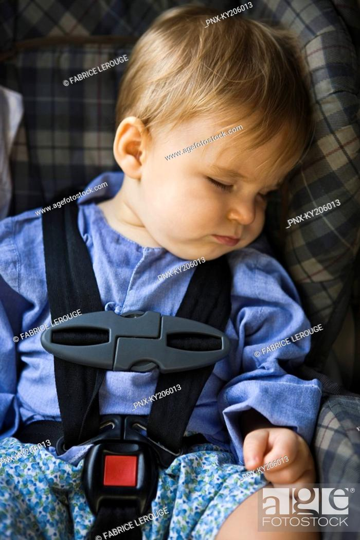 Stock Photo: Baby boy sleeping in a baby seat.