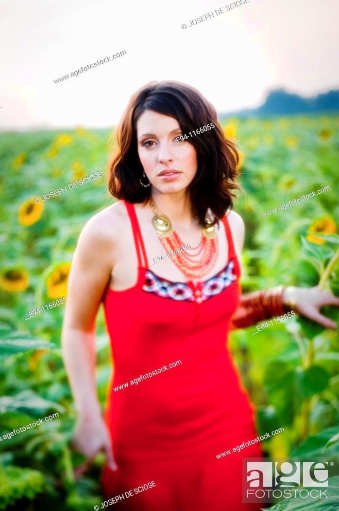 Stock Photo: 26 year old brunette woman wearing a red dress in a field of sunflowers.