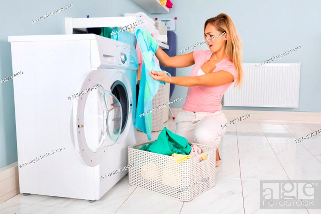 Stock Photo: Young Woman Looking At Clothes After Washing In Washing Machine At Utility Room.