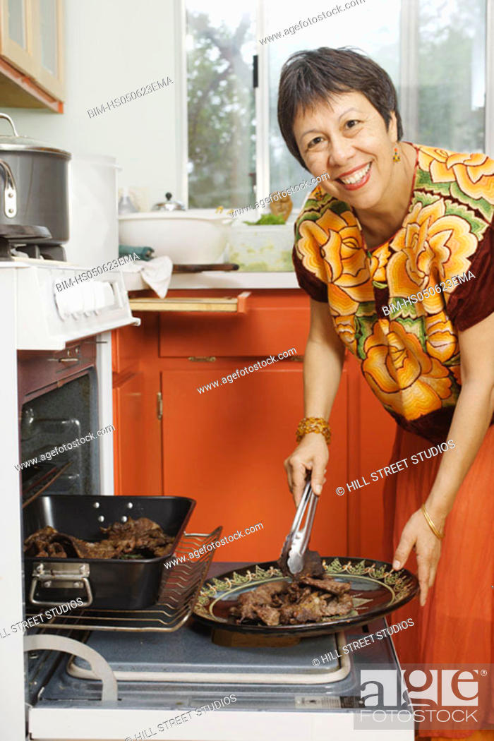 Stock Photo: Woman putting cooked meat onto a plate.