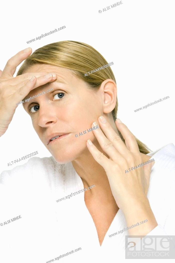 Stock Photo: Mature woman examining her face, close-up.