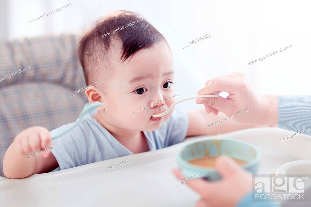 Stock Photo: The lovely baby boy is eating.