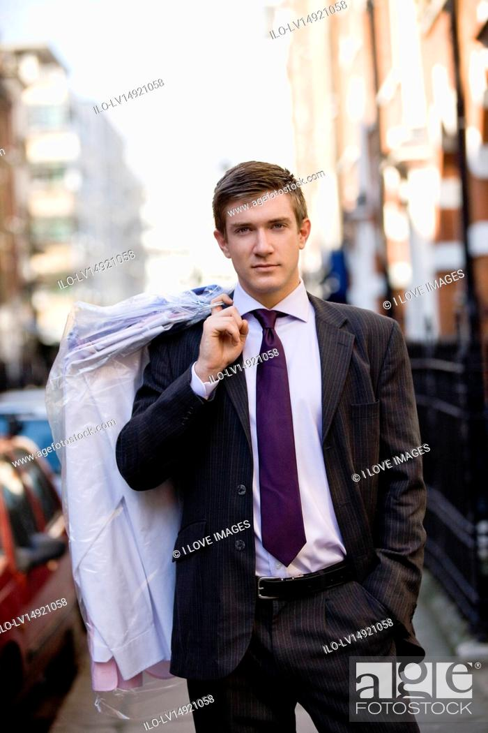 Stock Photo: A businessman carrying his dry cleaning.