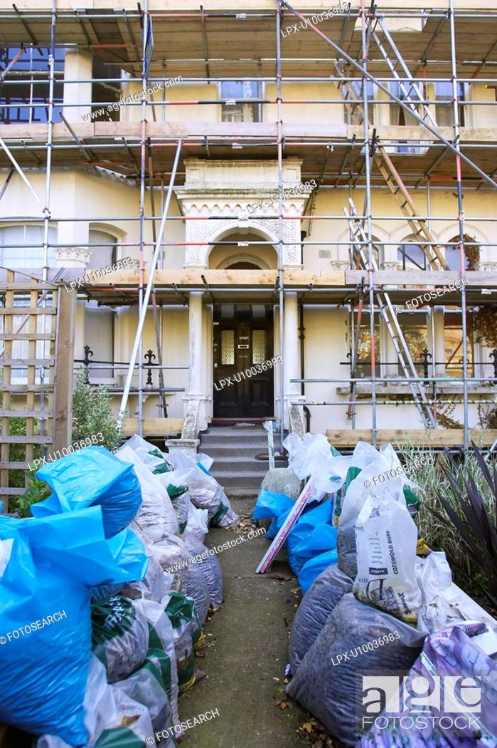 Stock Photo: Property under refurbishment with scaffolding and waste in the front garden.