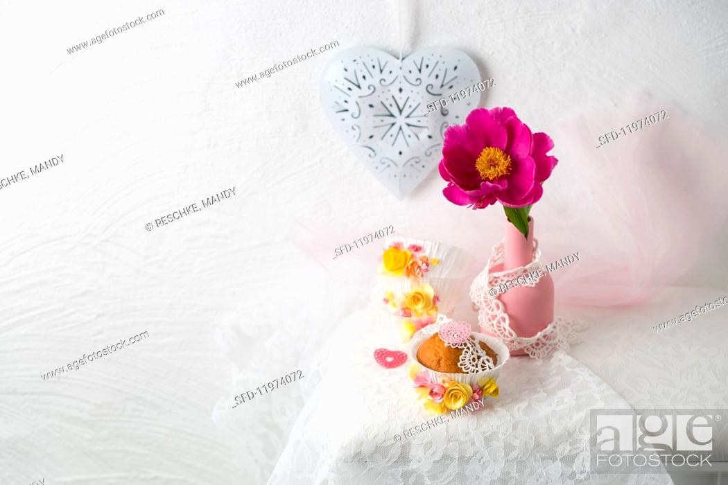 agefotostock & A cupcake decorated with paper flowers in front of a peoney ...