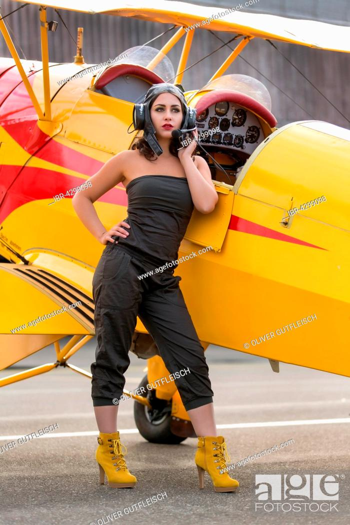 Stock Photo: Young woman in green jumpsuit and old flying cap poses with yellow biplane, Fashion.