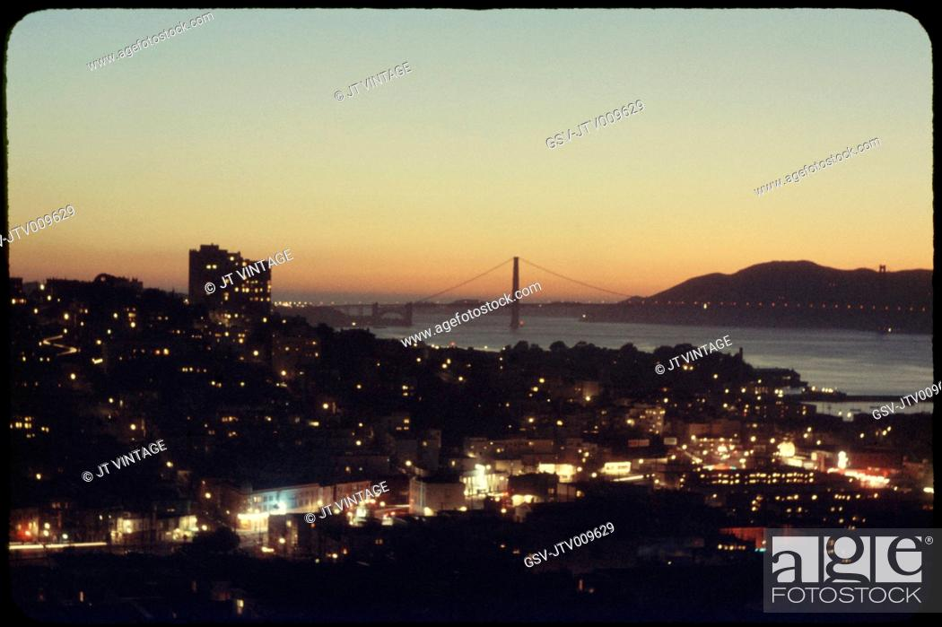 Imagen: Illuminated Cityscape with Golden Gate Bridge in Background at Sunset, San Francisco, California, USA, 1957.