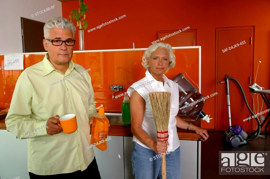 Stock Photo: Senior couple with cleaning utensils in the kitchen.