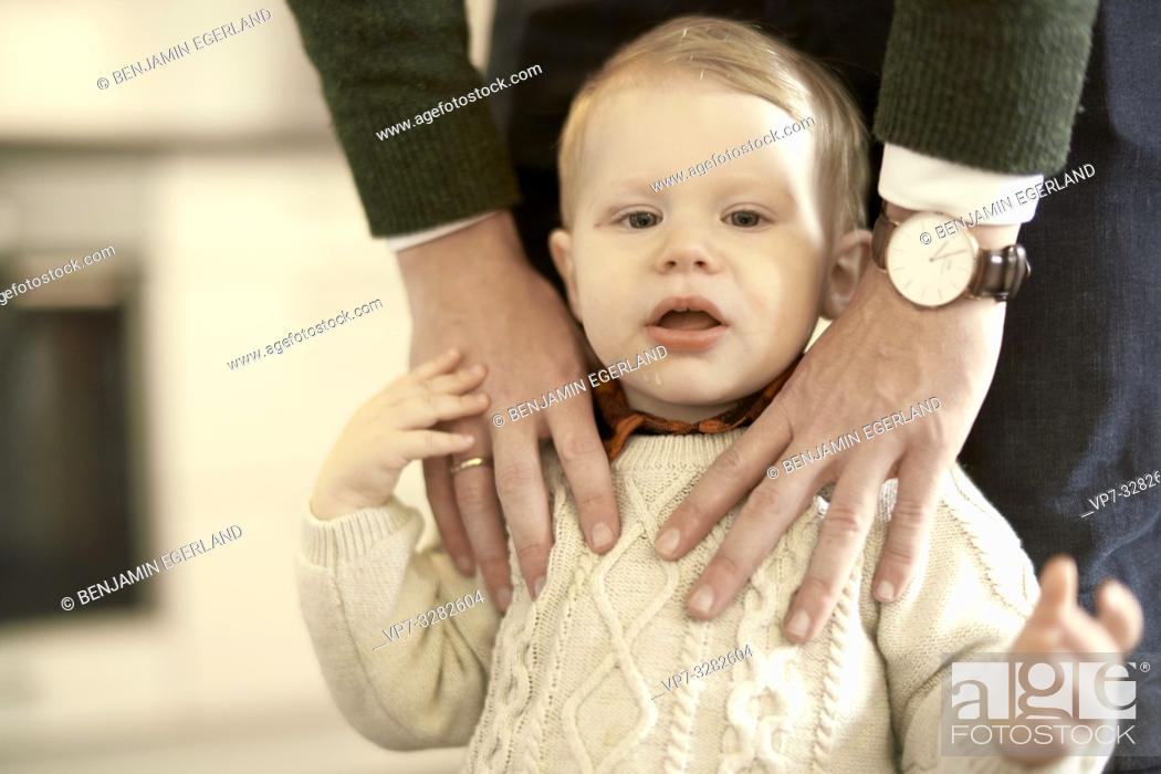 Imagen: baby toddler child with hands of caring father on him, in Cottbus, Brandenburg, Germany.