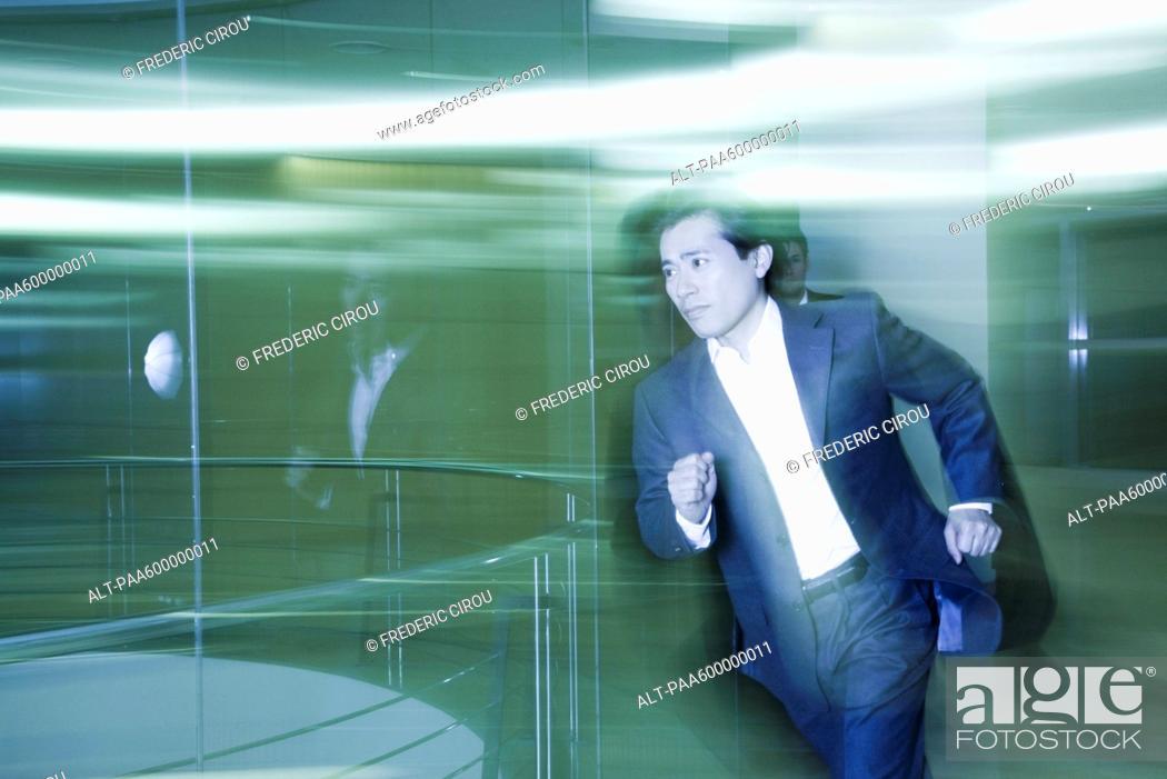 Stock Photo: Businessman running in lobby.