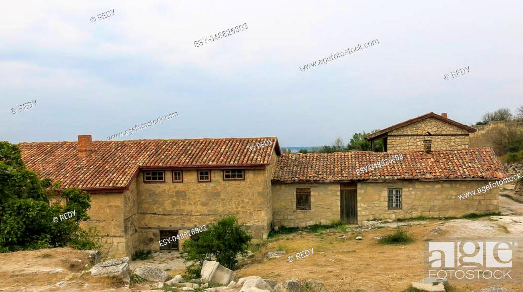 Stock Photo: old stone farmhouse with outbuildings with tiled roof.
