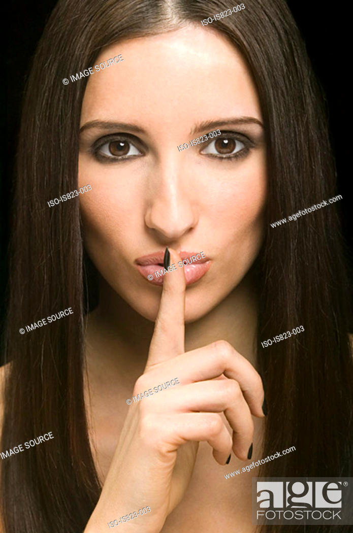 Stock Photo: Beautiful woman with finger to mouth.