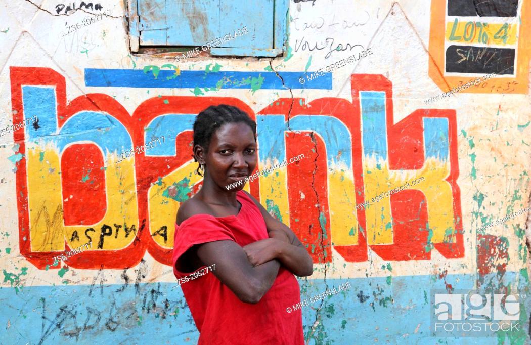 Imagen: Portrait of woman outside a bank sign, Isle de la Gonave, Haiti.