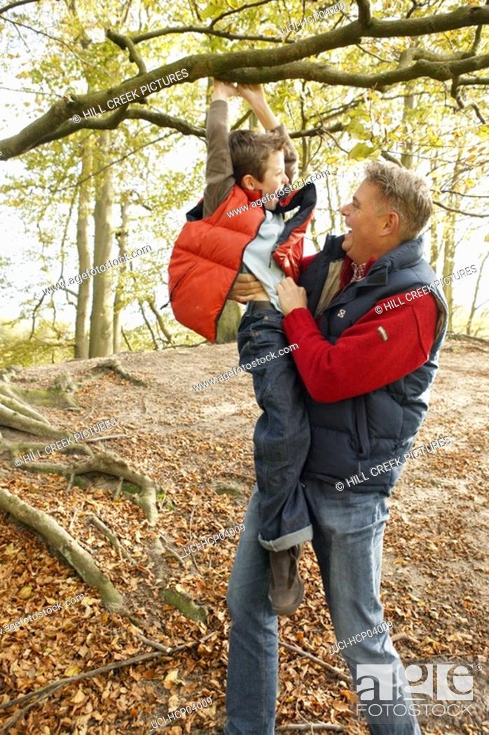 Stock Photo: Father and son playing on tree.