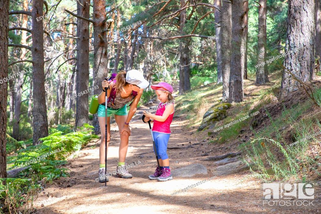 Photo de stock: mountaineer family laughing (woman and five years old girl), with caps and trekking sticks, on a footpath in a forest of Canencia (Madrid, Spain, Europe).