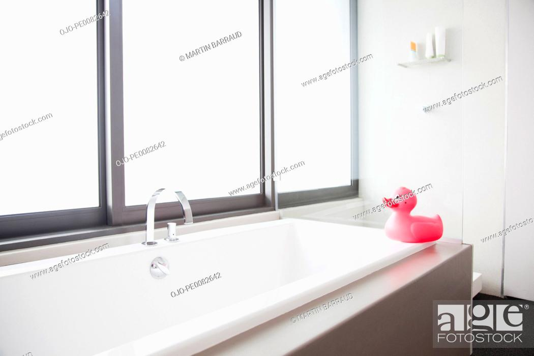 Stock Photo: Pink rubber duck at edge of bathtub in modern bathroom.