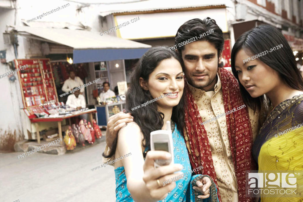 Stock Photo: Close-up of a young man and two young women taking a photograph of themselves.